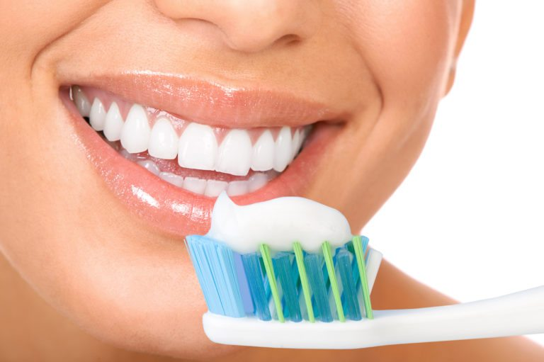 Tooth brush with tooth paste in front of smiling woman