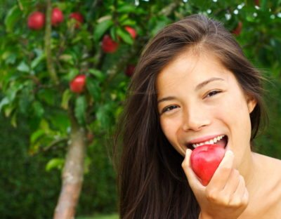 Picture of girl able to eat an apple after having had dental implants applied