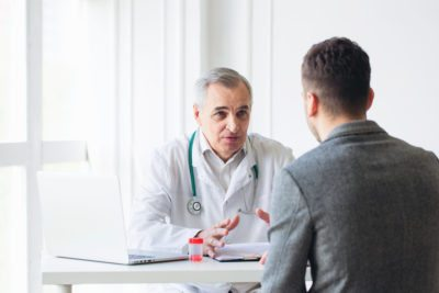 Doctor and patient sitting at table discussing oral pathology