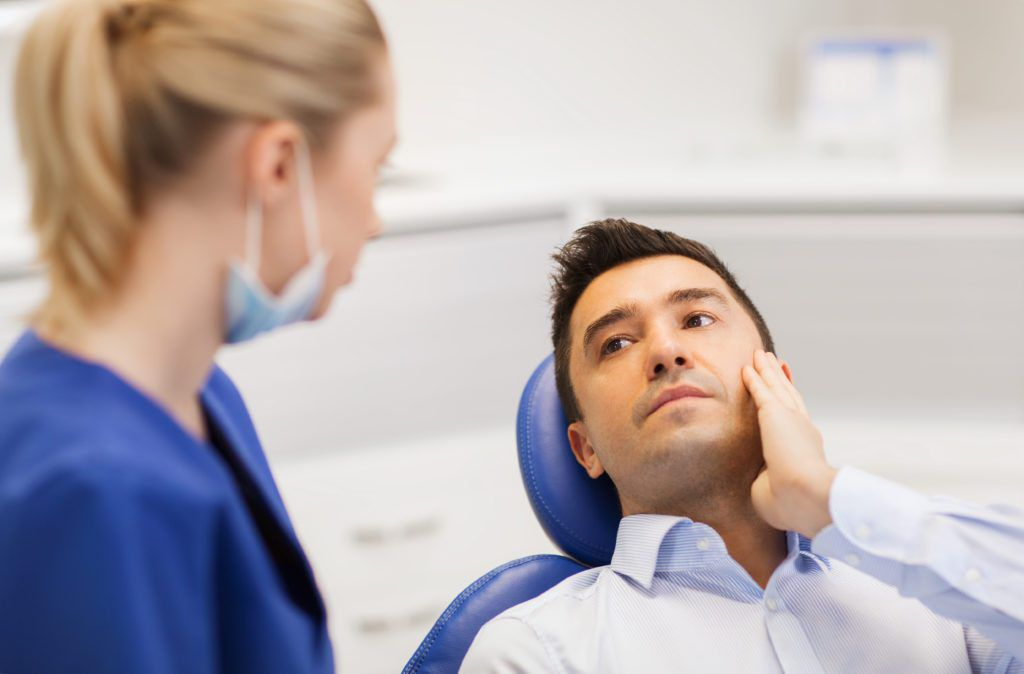 Dentists talking to patient in dental chair